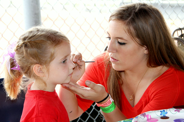 Loralei Martin has her face painted by Paige Koester at the St. Anthony Parish Picnic Sunday afternoon.<br /> Tony Huffman photo