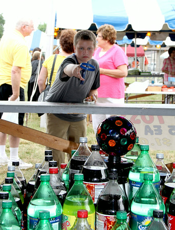 Michael Combs tries his hand at the soda throw during the St. Anthony Parish Picnic Sunday afternoon.<br /> Tony Huffman photo