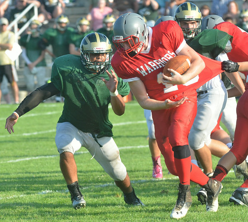 WARREN DILLAWAY / Star Beacon ALEX STURGILL (with) ball of Edgewood gets slowed by a Lakeside defender as Dragon Tyree Meeks (left) closes in on Friday at Corlew Field in Ashtabula Township.