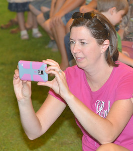 WARREN DILLAWAY / Star Beacon SARAH LOVELAND, of Roaming Shores, takes pictures during the frog jumping contest at the 124th Pierpont Picnic in Pierpont Township on Saturday.