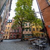 picturesque setting, on a cobbled square, beside a chestnut tree, surrounded by ochre and yellow storybook houses. Gamla Stan, Stockholm, Sweden. Sept. 30, 2019