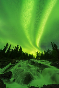 Aurora spotlight through the clouds, Cameron river rampart falls, Canada
