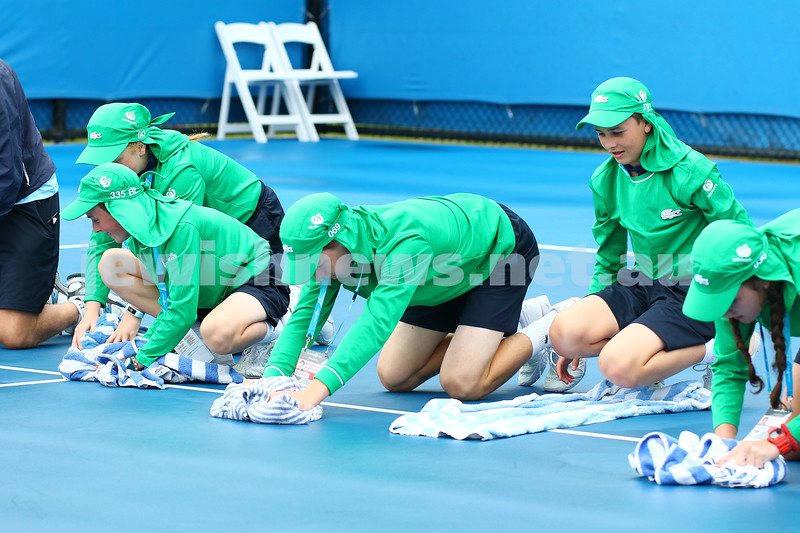 14-1-16. Australian Open Womens Qualifying round 1. Ball kids mop up the wet court after a rain delay. Photo: Peter Haskin