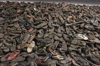 Victim's shoes behind a glass panel. This image shows about one third of all the shoes on display, which is only a portion of what was found. With thousands being killed every day, the piles of discarded items grew quickly.