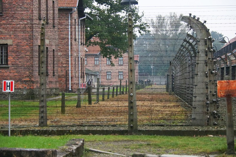 Formidable fences line the primary detention blocks on all sides. The faded, orange rusty sign at right is period correct, possibly original,  and says DANGER- HIGH VOLTAGE in German.