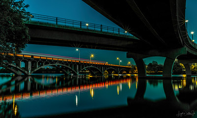 Lamar Street bridge with the reflections on the lake of the red tail lights of the cars traveling across the bridge.