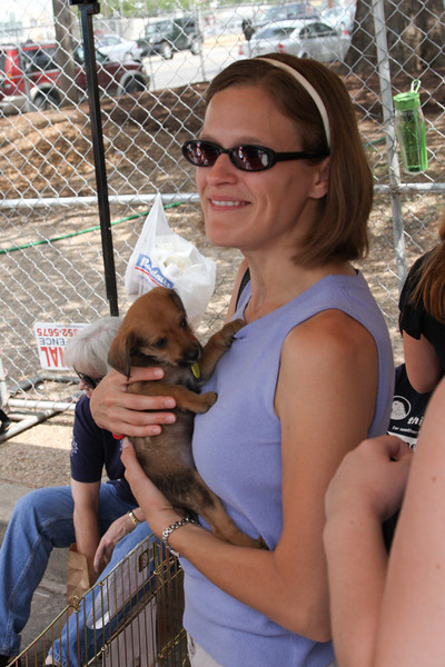 Visitors to the first adoption event at the market get lots of quality puppy cuddling time.