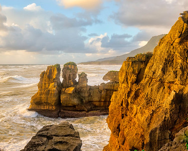 Sunset warms the dramatic cliffs at Punakaiki