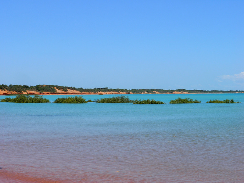 Blue water over red sand