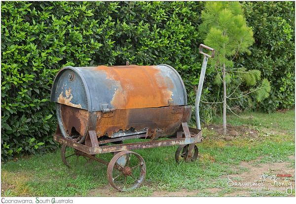 Rusty metal wheelbarrow with old barrel