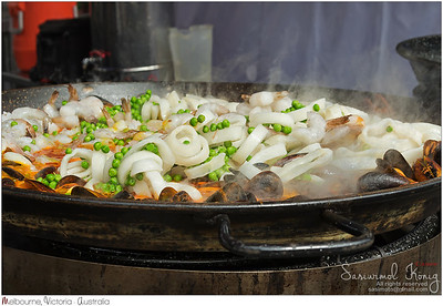 Valencian rice dish, seafood paella - sliced squids, shrimps, mussels, green beans being cooked in a large shallow pan