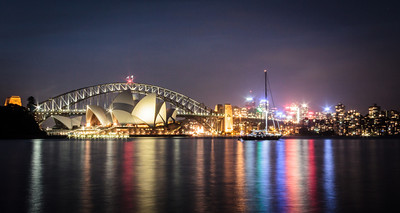 The Sydney Opera House and lights of downtown Sydney reflect in Sydney Harbour