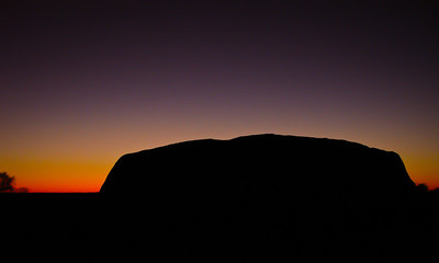 The rising sun creates a colorful, dramatic backdrop behind the silhouette of Uluru