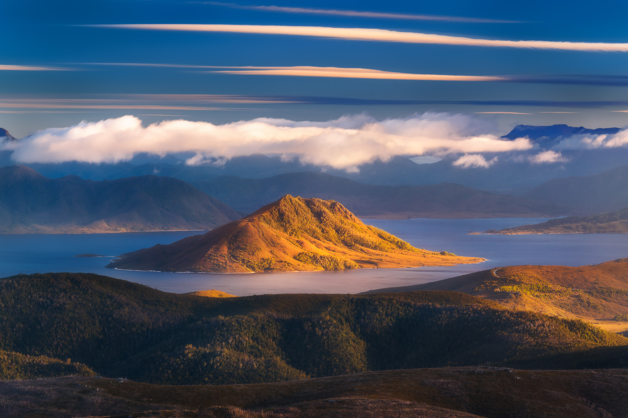 Strata : Layers of cloud , land and light featuring Scott's Peak and Lake Pedder
