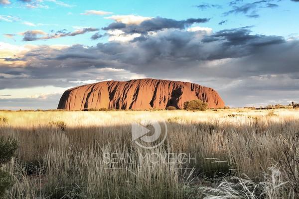 Uluru - Ayer's Rock rises from the desert grass