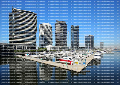 Dramatic downtown Melbourne, Australia waterfront skyline, with tall skyscrapers in the background and vessels anchored in the foreground.