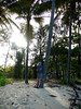 Near Sunset, Peter leans on a coconut palm, across the quiet street from our apartment building at Clifton Beach, near Cairns, Queensland, Australia.