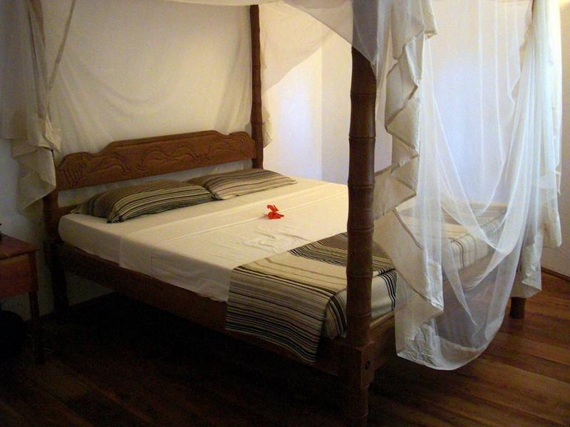 Bed with mosquito netting<br /> Aquarius Beach Resort, Watamu, Kenya