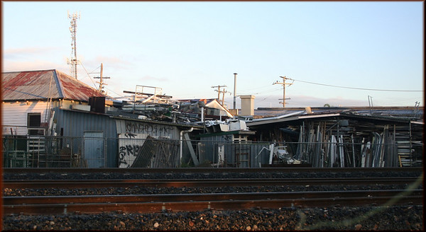 A view of a back of a shop, from the train, near Coorparoo Station ... they are running out of space .... supplies are even stored on the roof !!!