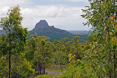 Mt Tibrogargan at the rear with Mt Tibberoowuccum in the foreground  Mt Tibberoowuccum (220m) is composed of alkali rhyolite. The mountain is a dome-shaped rock surrounded by eucalypt open forest, as well as complex rainforest.  Taken from Glasshouse Mountains Lookout - February 2010