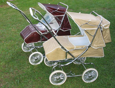 "Two different Regals - A 1975 ""Claret"" and the 1979-80 Beige version. You can see the different, straighter style foot cover on the beige pram where it wraps around the front. The steel footrests on the prams were redesigned around this time and the front cover was changed to accommodate the newer style."