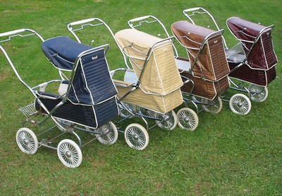 "1970's Steelcraft prams, three Regals and the reversible ""Consort"" model (gold). Left to Right:  1973 model P677 (regal) in 'Navy Calf' vinyl - first version with the larger, plastic molded wheels.  1978 model P677 (regal) in Beige vinyl - 2nd last regal version with the white edging / interior. 1974 model P696 (consort) in 'Gold Colonial' vinyl - first consort with plain white interior vs 'goldstar' from 1968. 1975 model P677 (regal) in 'Claret' vinyl (has the marble / mottled effect) plain white interior."