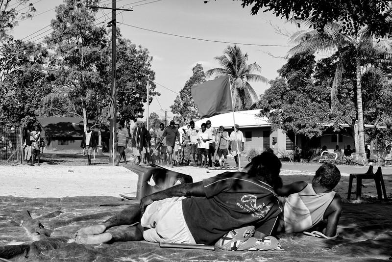 L'arrivée d'une procession devancée par des musiciens (joueur de didgeridoo à droite) dans la communauté de Gapuwiyak à l'occasion d'une cérémonie funéraire. Terre d'Arnhem/Territoire du Nord/Australie