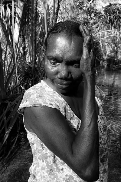 Zelda Gurruwiwi se rafraîchissant avec l'eau sacrée de la Rainbow Serpent River. Terre d'Arnhem/Territoire du Nord/Australie