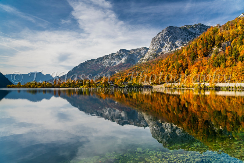 Fall foliage color in the trees and the calm lake with reflections at Grundlsee, Austria, Europe.