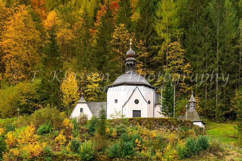 Church buildings on a hillside with fall foliage color in Hallstatt, Austria, Europe.