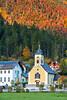 The village Pfarramt Catholic Church with fall foliage color in Obertraun, Austria, Europe.