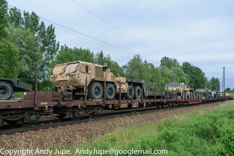 A HEMTT (Heavy Expanded Mobility Tactical Truck), part of the 500th Engineer Company / 15th Engineer Battalion / 18th Military Police Brigade) heads East through Leipzig Thekla station on Tuesday the 9th of June 2015 on board Austrian registered wagon Rns-z 31 81 3504 084-4