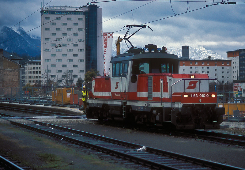Station pilot OBB 1163.010 runs past the building work at the east end of Salzburg Hbf. on 12 November 2006