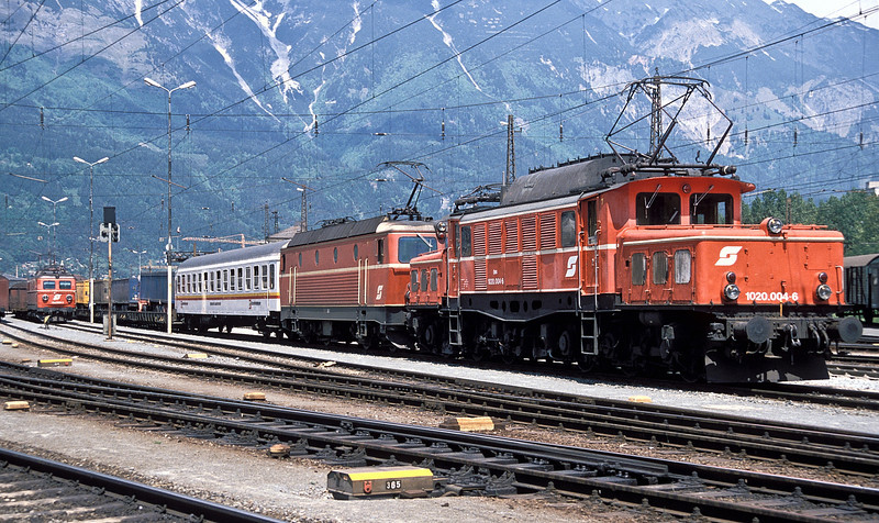OBB 1020.004 is seen at Innsbruck on 24 May 1989 waiting to pilot a 1044 and a swap-body 'rolling road' train over the Brenner line to Italy