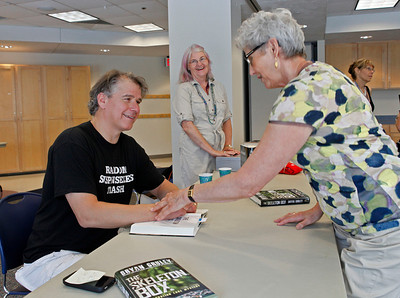 """Author Bryan Gruley chats with a reader as he signs a copy of """"The Skeleton Box."""" Gruley visited the Portage District Library to read and sign his recently published """"The Skeleton Box,"""" the latest of his Starvation Lake novels, on July 14, 2012.  Gruley, now at Business Week, had worked as a reporter at the Kalamazoo Gazette earlier in his career. (Courtesy of Bradley S. Pines / BSPines@gmail.com)"""