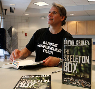 """Author Bryan Gruley signs a copy of """"The Skeleton Box."""" Gruley visited the Portage District Library to read and sign his recently published """"The Skeleton Box,"""" the latest of his Starvation Lake novels, on July 14, 2012.  Gruley, now at Business Week, had worked as a reporter at the Kalamazoo Gazette earlier in his career. (Courtesy of Bradley S. Pines / BSPines@gmail.com)"""