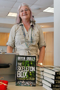 """Gloria Tiller, owner of Kazoo Books in Kalamazoo, Mich., smiles with copies of Brian Gruley's latest book. Gruley visited the Portage District Library to read and sign his recently published """"The Skeleton Box,"""" the latest of his Starvation Lake novels, on July 14, 2012.  Gruley, now at Business Week, had worked as a reporter at the Kalamazoo Gazette earlier in his career. (Courtesy of Bradley S. Pines / BSPines@gmail.com)"""