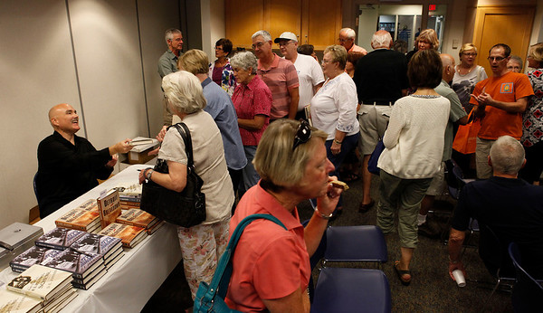 """Author Dan Johnson signs copies of his third historical mystery, """"Detroit Breakdown,"""" during a visit to the Portage, Michigan District Library for a talk on the release day of the book, Sept. 4, 2012.  (Bradley S. Pines /  bspines@gmail.com)"""
