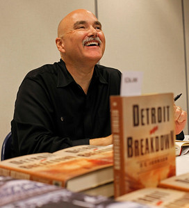 """Mystery author Dan Johnson smiles during a visit to the Portage, Michigan District Library to chat with readers and to celebrate the release day of this third novel, """"Detroit Breakdown,"""" on Sept. 4, 2012.  (Bradley S. Pines /  bspines@gmail.com)"""