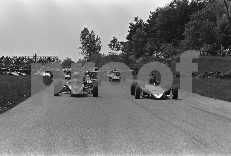 """At this point the cars are coming out of the small """"S"""" turn at Bluff Bend just before going into Turn 3. The spectator grandstand can be seen in the background."""