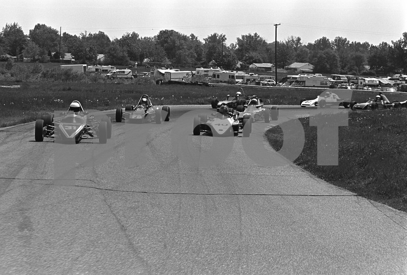 As the cars exit Turn 3, participant parking in the Paddock comes into view in the background. Turn 3 is also known as Skeet House Turn.