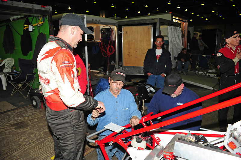 The Overhead Door crew works to get the 0 car back together after the throttle stuck during qualifying. This photo appeared in the January 28th edition of Area Auto Racing News.
