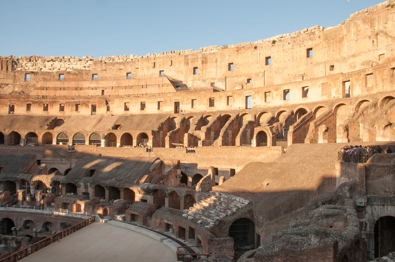 Interior of Colosseum where 50,000 Romans watched Gladiators, games, animal fights, etc. This lower part is being renovated to better show how it looked before the Colosseum was looted of it's marble. Lower left where the cross is is where the Emperor sat.