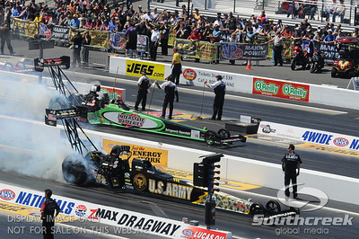 The top fuel dragsters driven by Tony Schumacher and Steve Torrence do their burn-outs before their semi-final race during the VisitMyrtleBeach.com NHRA Four-Wide Nationals Finals at zMax Dragway, Concord, NC.