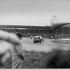 An Alan McKecknie Racing Ford Anglia chases Vic Elford in a Porsche
