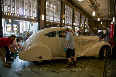 The 1934 Packard Twelve Model 1106 Sport Coupe is maneuvered through the lobby of the former post office.