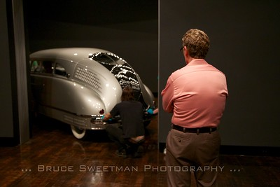 Frist Museum Chief Curator Mark Scala watches the 1936 Stout Scarab move into place on the gallery floor.