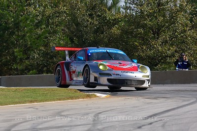 The #44 Flying Lizard Motorsports Porsche 911 GT3 RSR hops over turn 3.