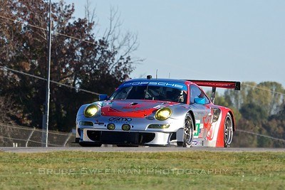 The #44 Flying Lizard Porsche GT# RSR crests the hill above turn 1.