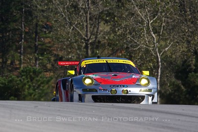 The #45 Flying Lizard Motorsport 911 GT3 RSR Porsche crests the hill above turn 1.